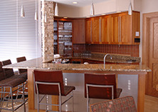 Kitchen with tables and chairs, wood cabinets, bar (2592 x 1944)